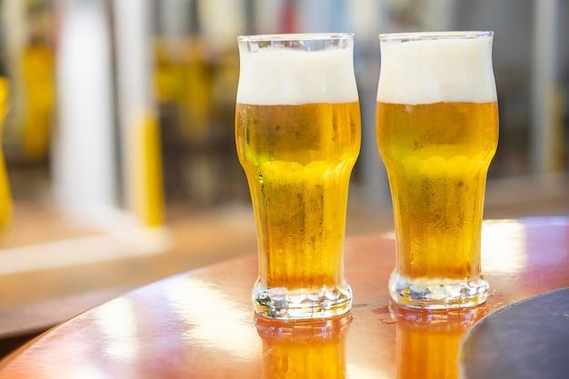 Dois copos de cerveja no topo da mesa de madeira