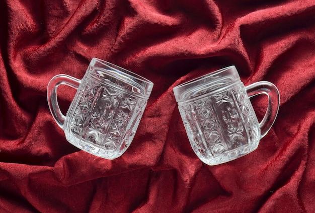 Dois copos de cerveja retrô vazios em um fundo de seda vermelho. vista do topo.