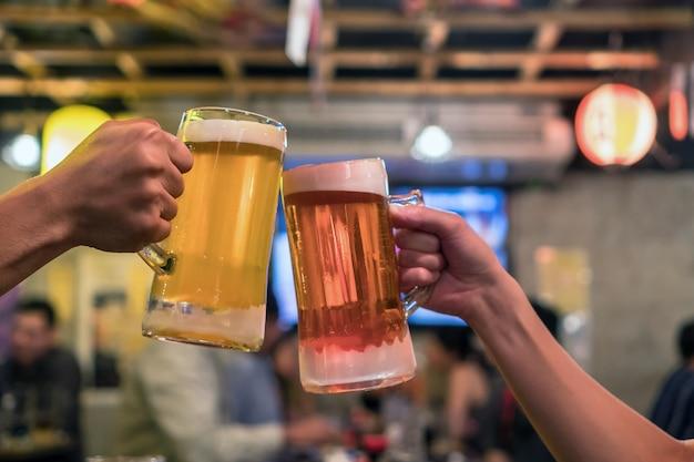 Dois copos de cerveja, um ao outro