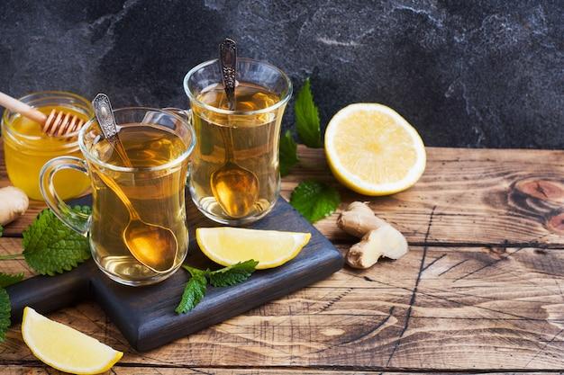 Dois copos de chá de ervas natural gengibre limão hortelã e mel em um fundo de madeira. copie o espaço