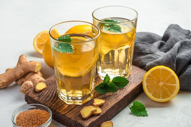 Dois copos de chá de gengibre saudável com limão em um fundo cinza. vista lateral, close-up.