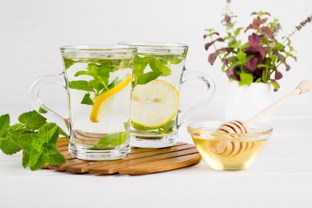 Dois copos de chá de hortelã fresca com limão e um monte de hortelã em um vaso