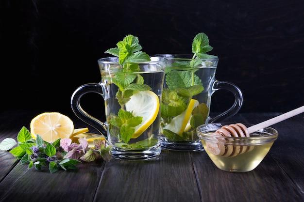 Dois copos de chá de menta fresca com limão e mel na mesa escura