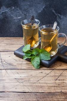 Dois copos de chá de menta numa superfície de madeira.