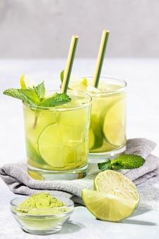 Dois copos de chá matcha verde gelado com limão, gelo, hortelã, canudos de bambu em cinza claro.