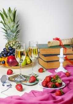 Dois copos de champanhe na mesa de madeira branca com livros antigos e relógio, diferentes frutas tropicais e morangos