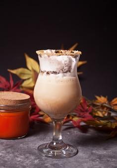 Dois copos de chocolate quente e cremoso com espuma com folhas de outono e abóboras