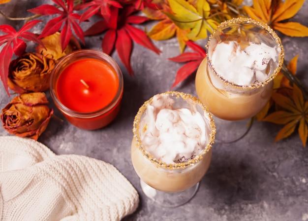 Dois copos de chocolate quente e cremoso com espuma com folhas de outono e vela