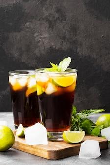 Dois copos de cocktail cuba libre em um fundo escuro