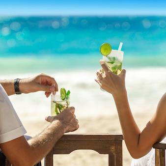 Dois copos de cocktail nas mãos no fundo do mar. conceito de férias de verão. mojito fresco na praia. descanse em férias no cinto. praça do instagram.