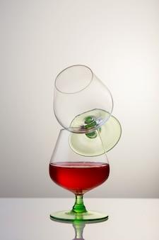 Dois copos de conhaque ou conhaque e a garrafa na mesa de madeira.