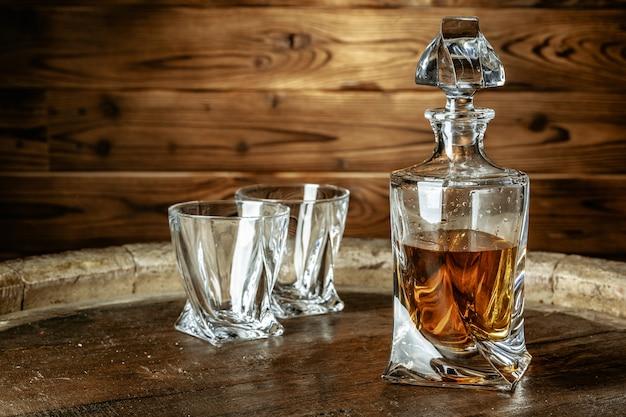 Dois copos de conhaque ou conhaque e garrafa na mesa de madeira