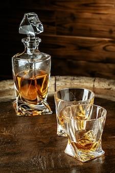 Dois copos de conhaque ou conhaque e uma garrafa na mesa de madeira
