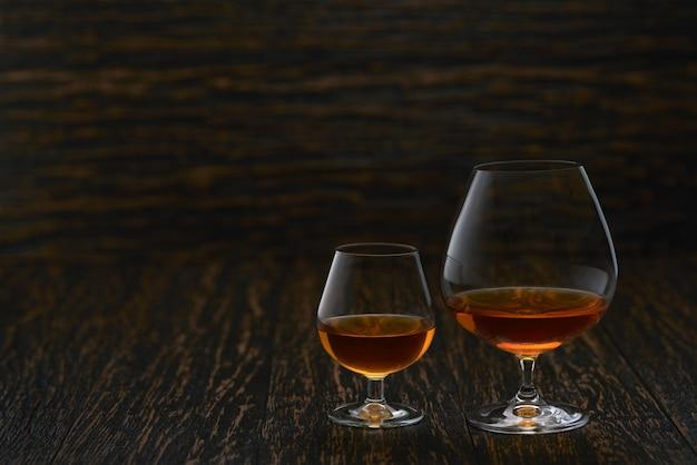 Dois copos de conhaque ou conhaque em uma mesa de madeira com espaço de cópia.