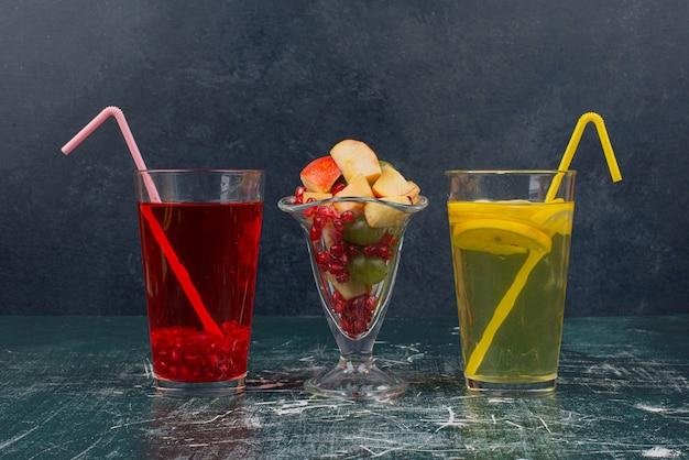 Dois copos de coquetéis com canudos e um copo de frutas mistas na mesa de mármore.