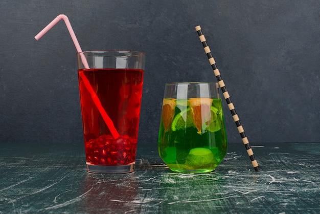 Dois copos de coquetéis com canudos na mesa de mármore.