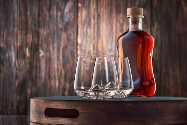 Dois copos de cristal e uma garrafa cheia de uísque