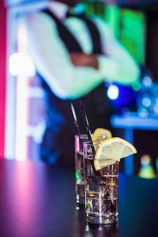 Dois copos de gim no balcão do bar e barman inclinando-se