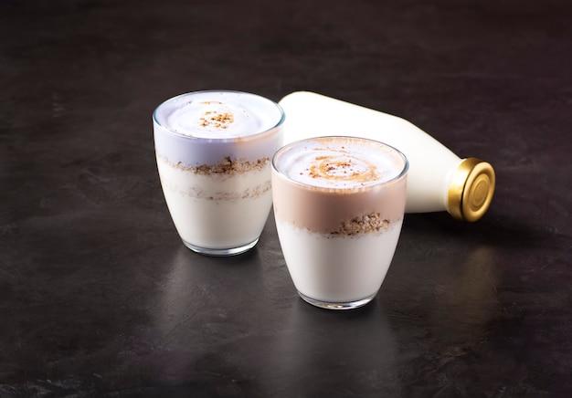 Dois copos de iogurte de kefir com granola estão na mesa.