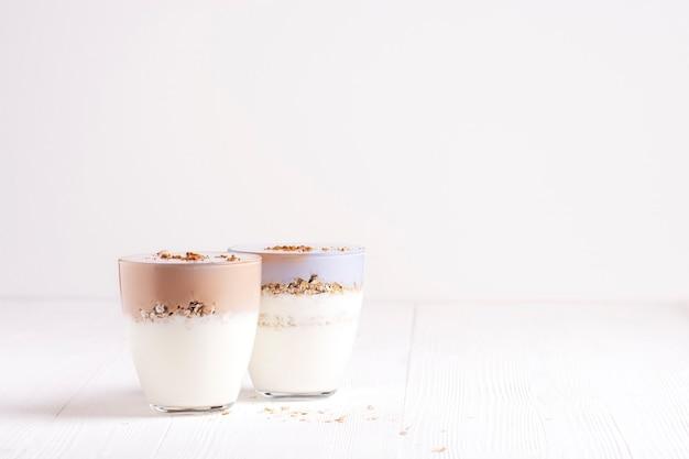 Dois copos de kefir caseiro com granola estão sobre uma mesa de madeira branca.