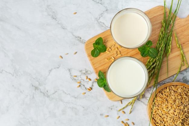Dois copos de leite de arroz com planta de arroz na borda de madeira ao lado da tigela de sementes de arroz