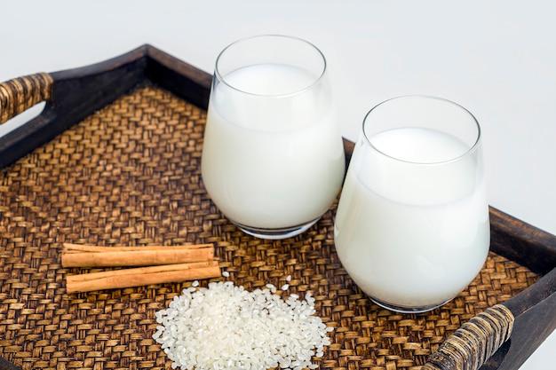 Dois copos de leite de arroz vegatarian e grãos de arroz serviram em uma bandeja. revigorante café da manhã saudável. leite alternativo não lácteo. conceito de nutrição adequada e alimentação saudável. comida orgânica.
