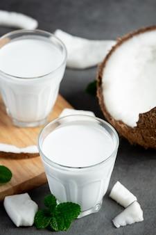 Dois copos de leite de coco colocados em fundo escuro