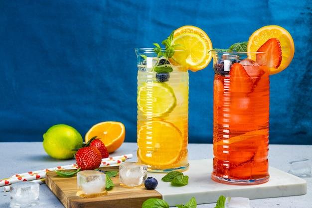 Dois copos de limonada refrescante de verão com gelo. coquetel com morango e limão e coquetel com limão e lima