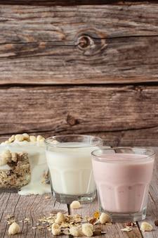 Dois copos de morango saudável e iogurte clássico com aveia na mesa de madeira