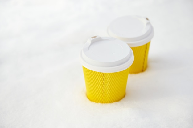 Dois copos de papel para viagem amarelos com bebida quente em uma neve branca e fofa no parque de inverno