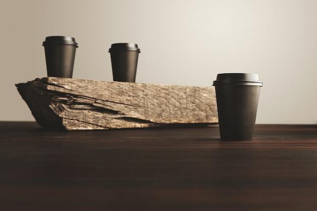 Dois copos de papel pretos desfocados levam embora com tampas fechadas isolados em um tijolo de madeira na mesa