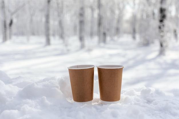 Dois copos de papel sem logotipos e inscrições com chá, café ou chocolate quente na neve no inverno. conceito de bebida quente de rua.