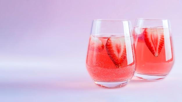 Dois copos de sangria de morango com espumante, morango e cubos de gelo em taça de champanhe