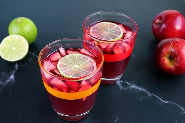 Dois copos de sangria de vinho tinto na mesa com limão borrado e maçãs ao fundo