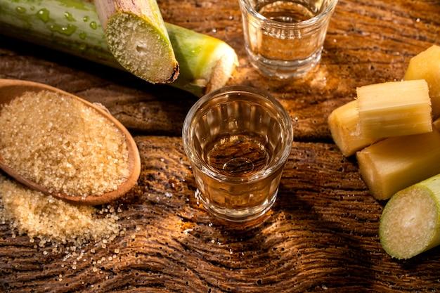 Dois copos de shot de cachaça brasileira de ouro com açúcar e cana-de-açúcar isolada em espaço rústico de madeira.