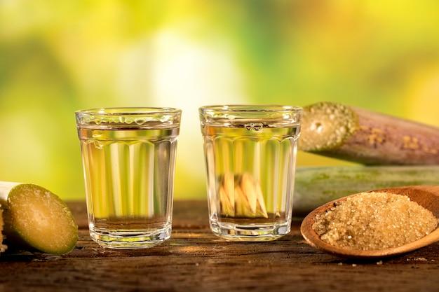Dois copos de shot de cachaça brasileira de ouro com açúcar e cana-de-açúcar isolada em fundo de madeira rústico