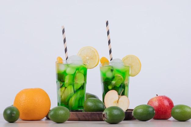 Dois copos de suco com fatias de frutas e frutas frescas.