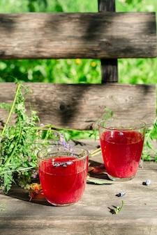 Dois copos de suco de frutas frescas de madressilva caseiro servido em madeira