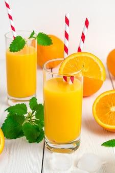 Dois copos de suco de laranja com tubos, hortelã e laranjas frescas em uma mesa branca.