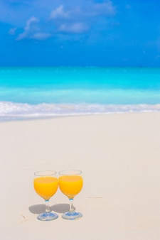 Dois copos de suco de laranja na praia tropical branca
