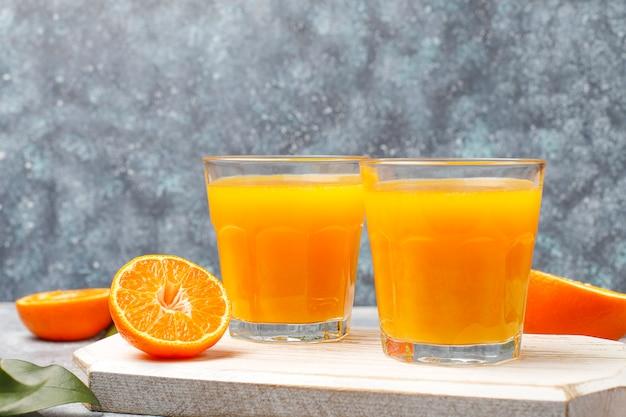 Dois copos de suco de laranja orgânico fresco com laranjas cruas, tangerinas