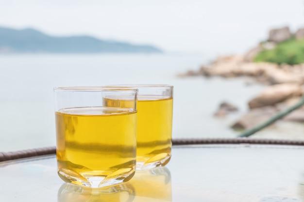 Dois copos de suco de maçã fresco na mesa perto do mar.