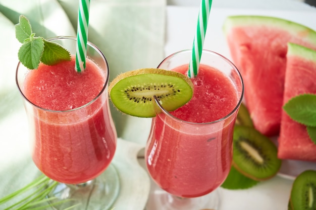 Dois copos de suco de melancia com kiwi e hortelã em uma mesa branca