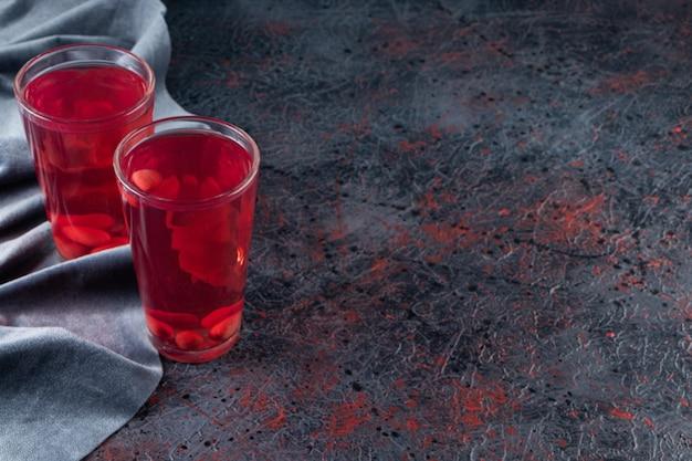 Dois copos de suco em um pedaço de tecido, na mesa mista.