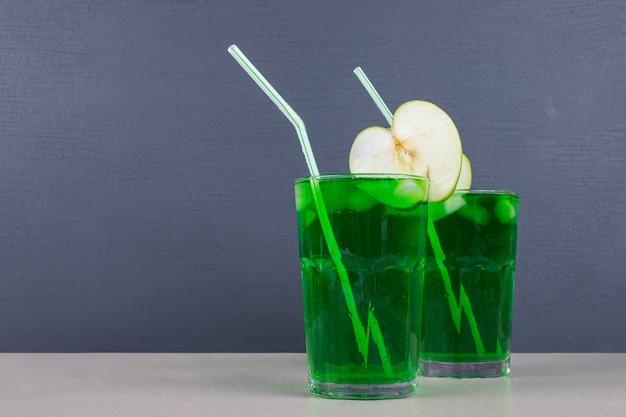 Dois copos de suco verde com canudos na mesa azul.