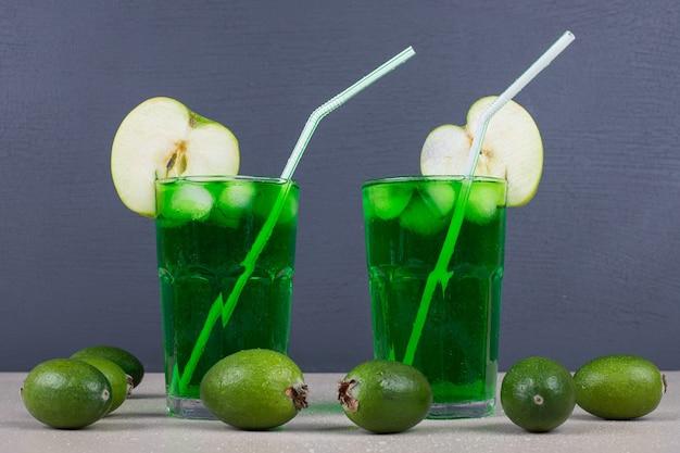 Dois copos de suco verde com canudos na parede azul.