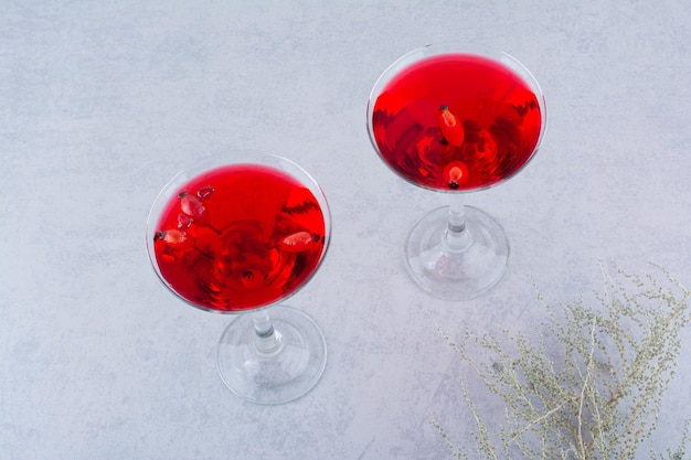 Dois copos de suco vermelho em fundo de pedra. foto de alta qualidade