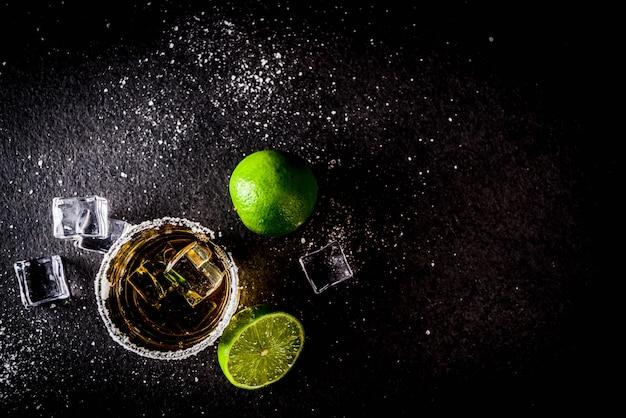Dois copos de tequila na mesa escura, com cubos de gelo, sal e limão