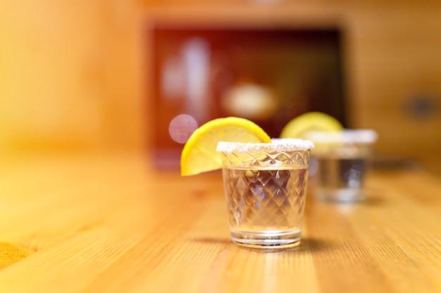 Dois copos de tequila no fundo de um laptop com assistir a um filme. noite agradável em casa.