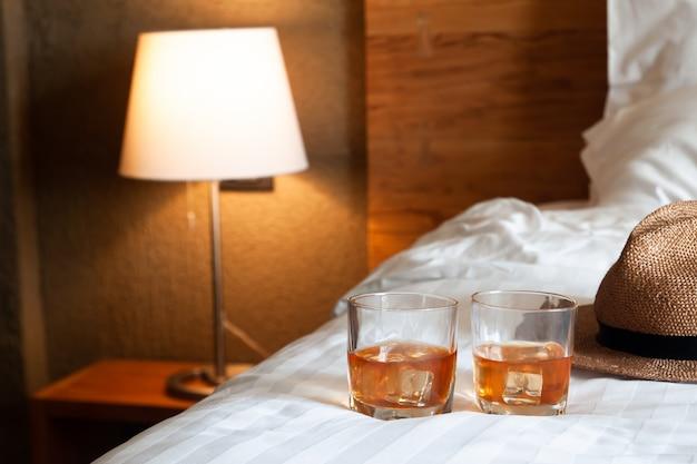Dois copos de uísque com gelo na cama e lâmpada de iluminação no fundo